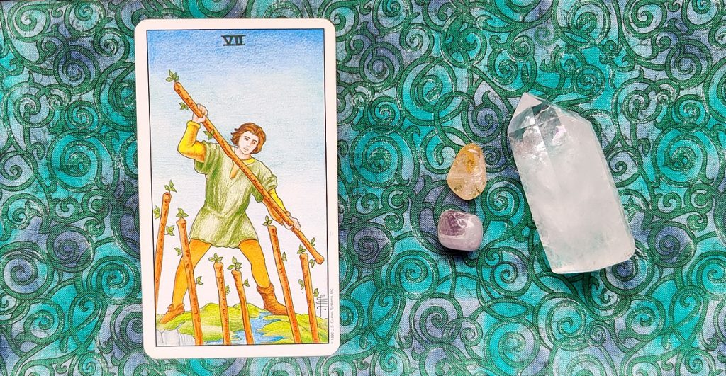 Seven of Wands card on a tarot cloth with crystals